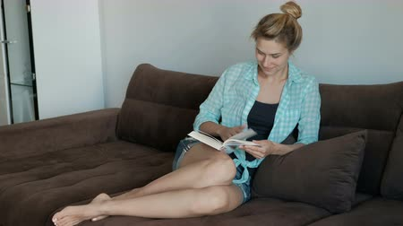 bacaklar : Young woman reading book sitting on sofa in apartment. Having settled on velor surface she holds in hands book.