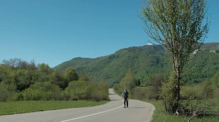 bruslař : Young man riding on longboard on country road in summer day.