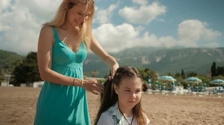 braid hair : Mom plaits pigtails daughter in nature landscape outdoors Stock Footage