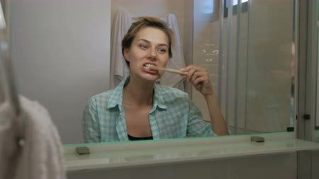 escovação : Young woman brushing teeth standing in bathroom in morning indoors. Vídeos