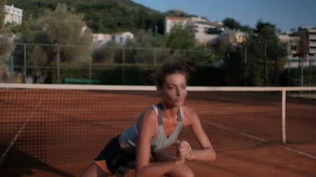 wizerunek : Young woman practicing before a tennis match in the open court.
