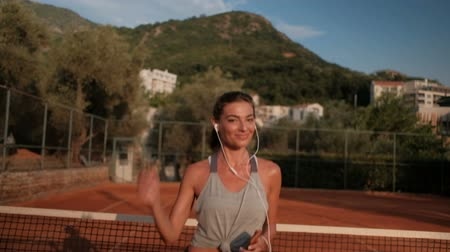 tennis stadium : Professional sportswoman jumping on tennis court listening music