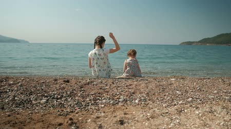 pigtail : Two girls sit on shore and throw stones into water in summer day outdoors.