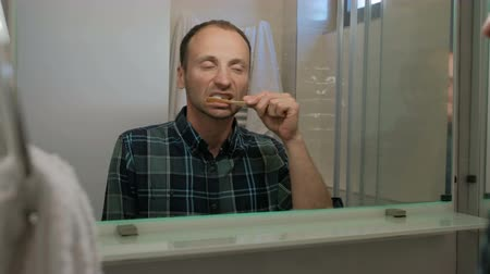 cotidiano : Young man brushing teeth while standing in bathroom indoors.