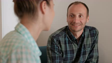 each other : Unshaven man smiles and asks questions the woman across the table. Stock Footage