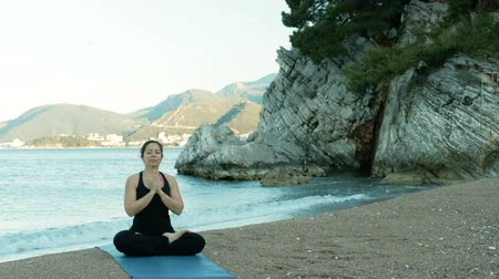 позы : An adult woman meditates with her eyes closed in a lotus pose on beach