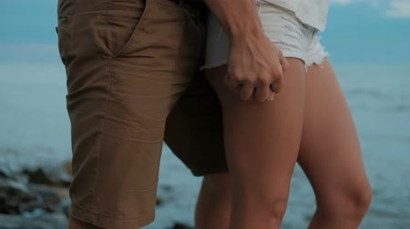 sposini : Man passionate hand squeezes women in short shorts on a rocky beach. On the sea coast a young couple stands and hugs.