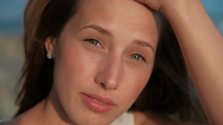 modelo de moda : Portrait of a young woman with flying red hair and without makeup. Beautiful lady with clean skin and blue-gray eyes looks carefully forward. Stock Footage
