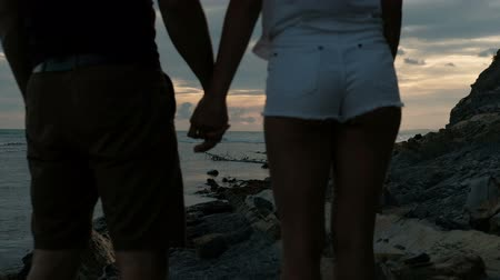 bastião : Man and woman hold hands and in evening watching sunset in sea. Loving couple in shorts standing on rocks and admiring summer sky in dark twilight.