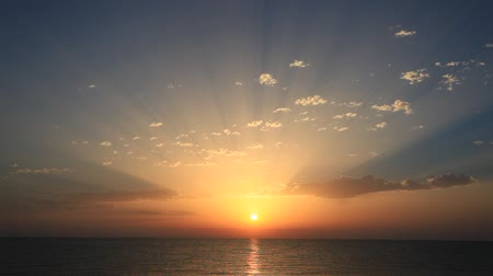 horizonte sobre a água : Perfect sunrise on the sea, with radiant rays of sun over a warm colorful horizon.