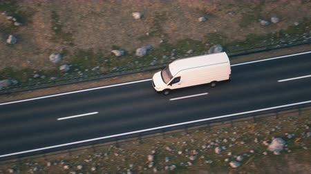 minibus : Aerial shot of a white delivery van driving along a desert highway into the sunset. Realistic high quality 3d animation. Stock Footage