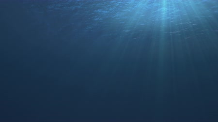 Seamless loop of a tranquil underwater scene with ocean waves and sun and light rays shining through - high quality 3d animation Stock Footage