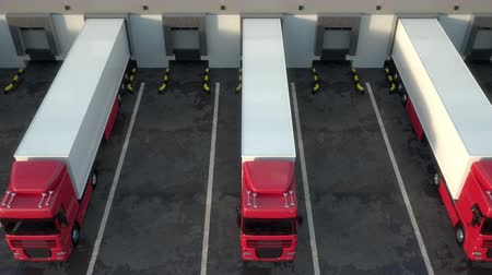 Red semi trucks loading and unloading goods at warehouse dock. Aerial view tracking shot. Seamless loop. Realistic high quality 3d animation.