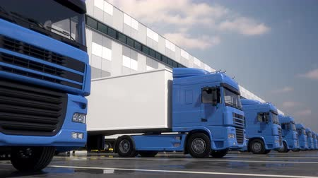 rakomány : Endless row of blue semi trucks loading and unloading goods at warehouse dock. Parallel tracking shot. Seamless loop. Realistic high quality 3d animation. Stock mozgókép