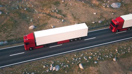 Aerial view of a convoy of semi trucks driving along a desert highway into the sunset. Realistic high quality 3d animation.