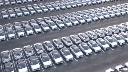 Aerial view of new electric self driving cars on car on a huge car dealership parking lot.  Multiple rows of electric cars for sale. New cars in storage. Realistic high quality 3d animation.