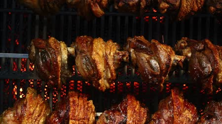 az yağlı : Several traditional Bavarian German roasted pork knuckles slowly cooked at rotating broiling rack grill spit, close up, low angle side view