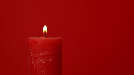 закалки : Close up one red candle trembling flame over vivid red background, off-center, fired up with lighter, burning and extinguished by man hand, low angle side view