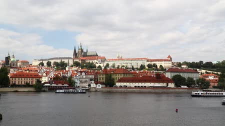 mala : Day view of Prague lesser old town (Mala Strana) with Royal castle palace and Saint Vitus Cathedral over Vltava river under blue sky