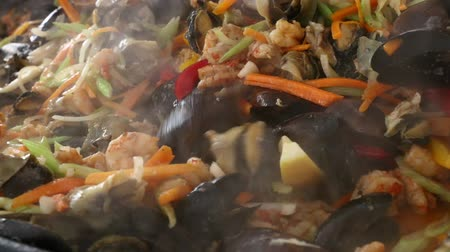 saute : Close up of cooking fresh seafood saute stew with shrimps, mussels and vegetables, stirring in big frying pan, close up, high angle view Stock Footage