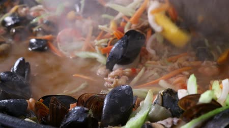 saute : Close up of cooking fresh seafood saute stew with shrimps, mussels and vegetables, stirring in big frying pan, close up, low angle view