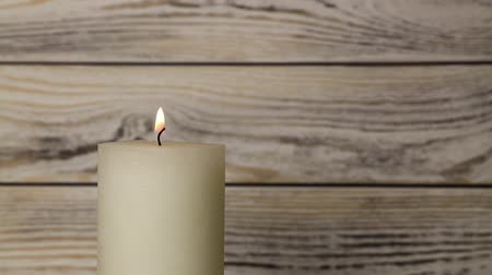 cera : Close up one white candle trembling flame over background of white and brown wooden planks wall, off-center, fired up with lighter, burning and blown out, low angle side view