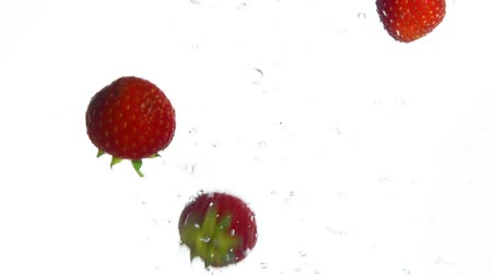 eper : Close up several fresh red ripe strawberries thrown and floating in clear transparent water, low angle side view, slow motion Stock mozgókép