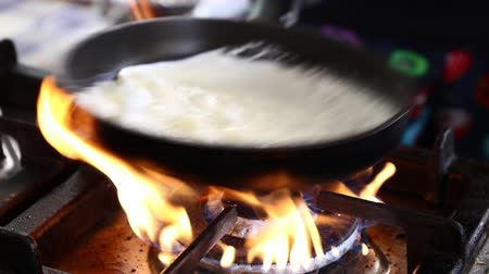 thicken : Close up cooking bechamel, Mornay or besciamella white sauce in a pan on flame gas stove cooktop, high angle view Stock Footage