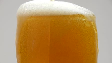 overfill : Close up background of pouring beer with bubbles and foam in glass, overfill and run out, flowing over the top, low angle side view, slow motion