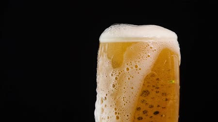 overfill : Close up background of pouring lager beer with bubbles and froth in glass over black background, overfill and run out, flowing over the top, low angle side view, slow motion