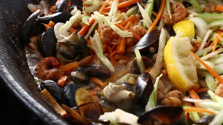 seafood dishes : Close up of cooking fresh seafood saute stew with shrimps, mussels and vegetables in big frying pan, close up, high angle view