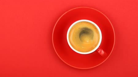 köpük : Close up one full cup of espresso coffee and saucer over vivid red paper background with slow motion animated cinemagraph spin of coffee froth, elevated top view, directly above