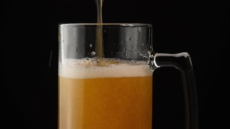overfill : Close up background of pouring lager beer with bubbles and froth in glass mug over black background, overfill and run out, flowing over the top, low angle side view, slow motion Stock Footage