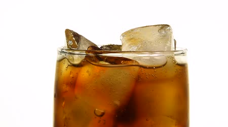 cola : Extreme close up full glass of carbonated cola soft drink with ice cubes over white background, low angle side view, slow motion Stock Footage