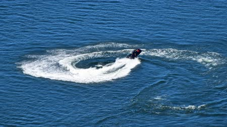jet ski : Cinemagraph of one man riding jet ski scooter over blue sea water with splash trace behind, high angle aerial view Stock Footage
