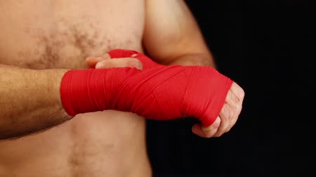 sıkmak : Close up man boxer tightening and testing red hand wraps over wrists preparing for fight, over black background, low angle front view Stok Video