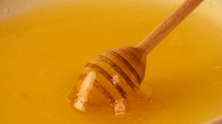 shovívavost : Close up spinning wooden honey dipper spoon in bowl of fresh thick fluid acacia honey, high angle view, slow motion