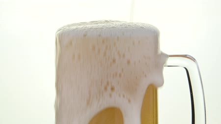 Close up pouring lager beer with bubbles and froth over the top in glass mug over white background overfill and run out low angle side view 4K Vídeos