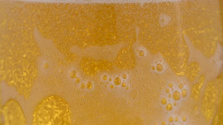 ale : Extreme close up background of pouring lager beer with bubbles and froth over the top in glass mug overfill and run out low angle side view slow motion Stock Footage