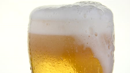 Close up pouring lager beer with bubbles and froth over the top in glass over white background overfill and run out low angle side view 4K Vídeos