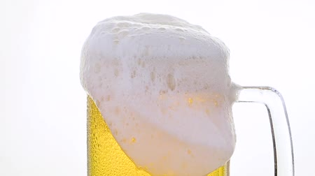 Close up pouring lager beer with bubbles and froth over the top in glass mug over white background overfill and run out low angle side view slow motion