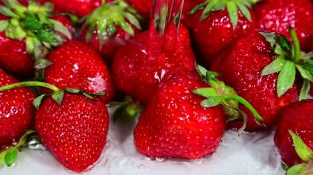 Close up washing heap of red ripe strawberry berries with water 4K