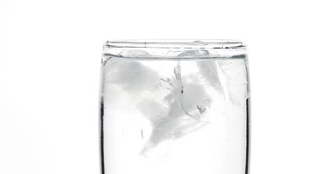 Close up ice cubes spinning in glass of pure clear sparkling water with gas over white background low angle side view slow motion