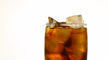 Extreme close up full glass of carbonated cola soft drink with ice cubes over white background low angle side view slow motion