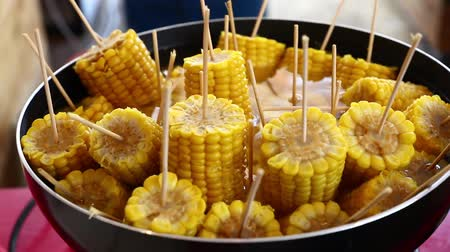 Closeup ready to eat boiled or steamed sweet corn cobs on stick in a big cooking pan high angle view
