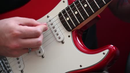 Close up Caucasian man musician playing red electric guitar plucking strings with pick low angle front view 4K