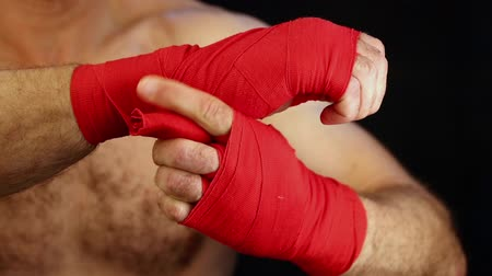 apertado : Close up man boxer wrapping red hand wraps over wrists preparing for fight over black background with copy space low angle view