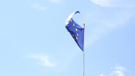 Close up flag of EU European Union waving and blowing in the wind over blue sky low angle view Vídeos