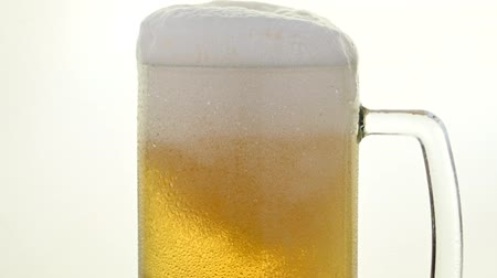 overfill : Close up pouring lager beer with bubbles and froth over the top in glass mug over white background, overfill and run out, low angle side view, slow motion