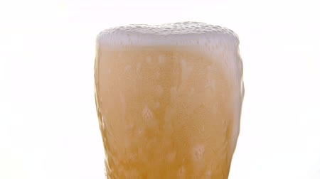 ale : Close up pouring lager beer with bubbles and froth over the top in glass over white background, low angle side view, 4K